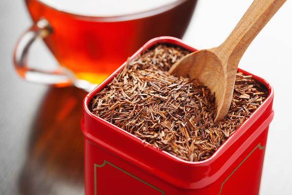 rooibos in tea tin box and wooden spoon closeup